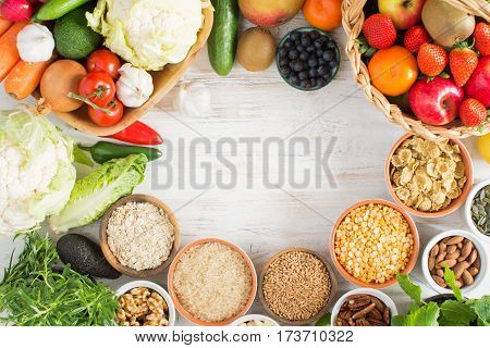 Variety of fruits and vegetables cereals nuts on the white wooden table top view copy space for text selecitve focus. Basket of strawberries apples oranges kiwi bowls of oats spelt rice kamut peas; broccoli cauliflower garlic tomatoes peppers
