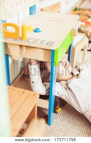 Girl playing in the repairer. Digging inside the device