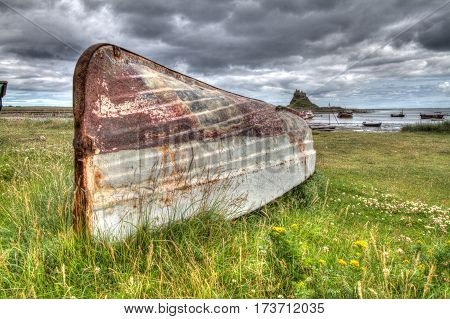 An aged boat upturned by Lindisfarne Castle