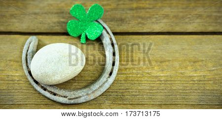 St Patricks Day shamrocks with horseshoe and pebble on wooden table