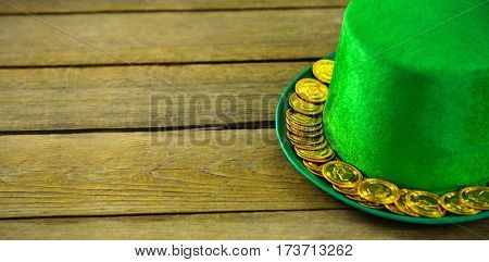 St Patricks Day leprechaun hat with gold chocolate gold coins on wooden wood