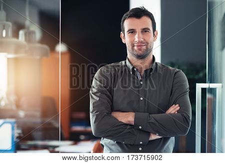 Portrait of a confident and successful young businessman smiling while standing with his arms crossed in a modern office