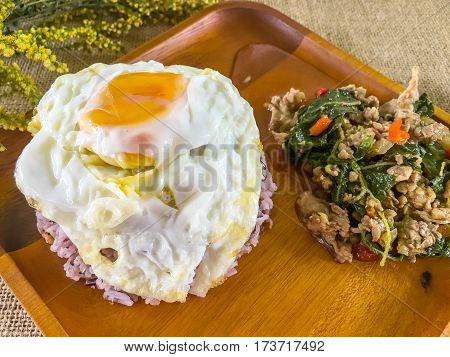 Rice topped with stir-fried pork and Ocimum sanctum with fried egg
