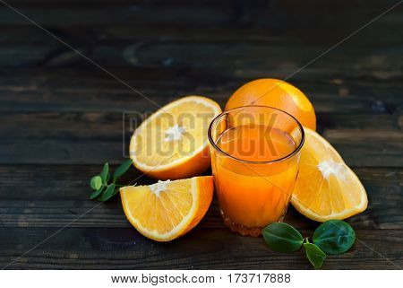 Glass Of Orange Juice And A Group Of Oranges On Dark Board