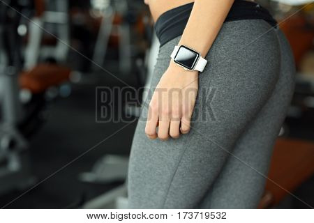 Young woman with fitness tracker in gym, closeup