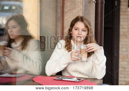 Woman is holding latte glass in her hand, outdoor cafe
