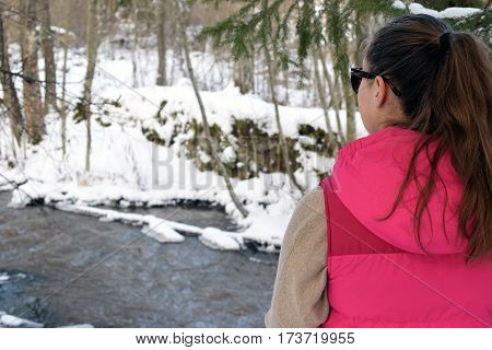 Young woman standing in wintry forest and watching a creek.