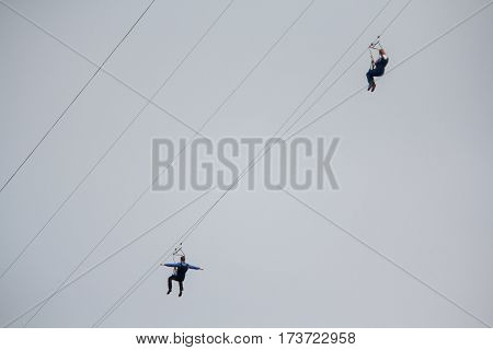 Couple down on ropes across the river. Extreme sports