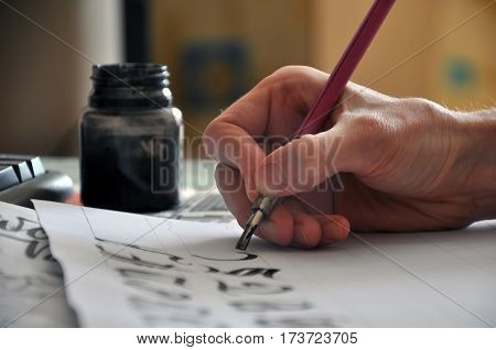Creating of manual calligraphy. Hand with pen and ink close up.