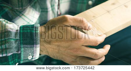 Man crafting using white glue wooden chair object keeping wooden boards in hands. Do it yourself project making process banner