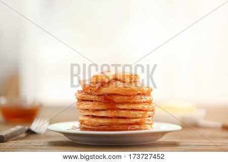 Delicious pancakes with butter and maple syrup on plate