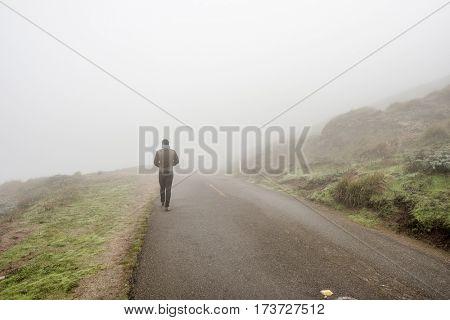 Lone man walking along the road through white fog