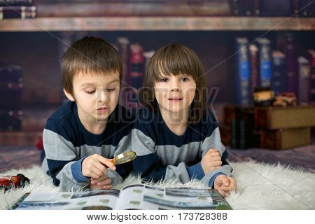 Two Little Children, Boys, Reading A Book With Magnifying Glass