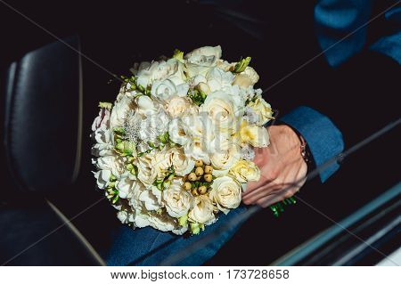 fiance in a dark blue suit sitting in a car with a wedding bouquet made of white roses
