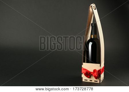 St. Valentine's Day concept. Wine bottle in gift box with satin ribbon on dark background