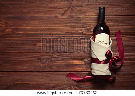 Decorated wine bottle on wooden background
