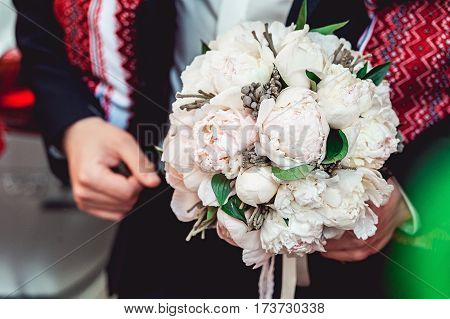 fiance in a dark shirt holding a wedding bouquet made of white peony