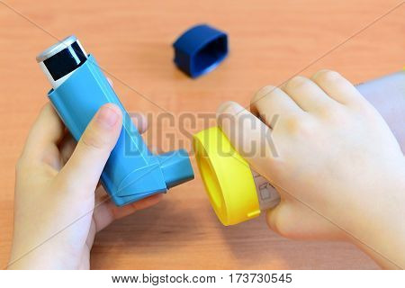 Small child holding asthma inhaler and spacer in his hands. Asthma spacer and aerosol inhaler for treatment and management bronchial asthma, allergy. How to use an inhaler with a spacer