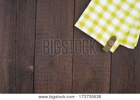 Green checkered tablecloth on wooden table. Top view.