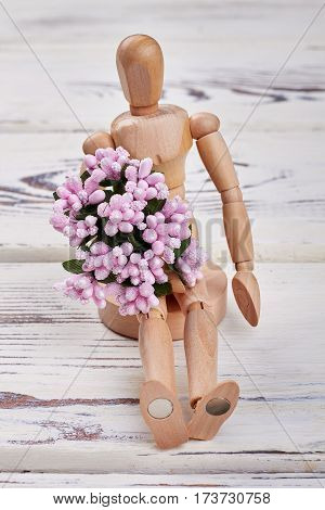 Wooden manikin with flowers. Simple surprise for woman.