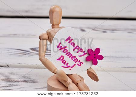 Manikin and heart-shaped card. Celebration of Women's day.