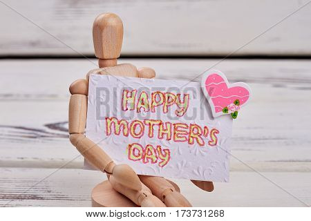 Manikin with greeting card. Mother's day congratulation.