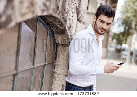 Young man using mobilephone on the street.