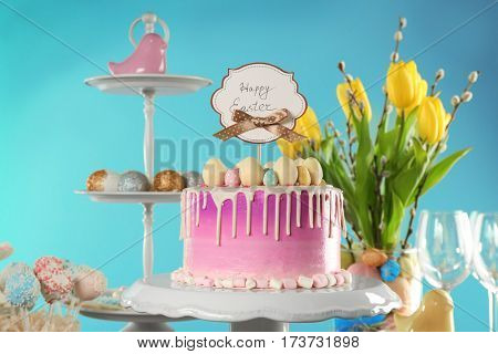 Delicious Easter cake decorated with colorful sweet eggs and greeting card on festive background