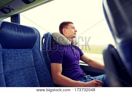 transport, tourism, road trip, rest and people concept - happy young man sleeping in travel bus with inflatable pillow
