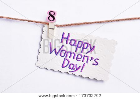Card hanging on clothesline. Creative surprise for Women's day.