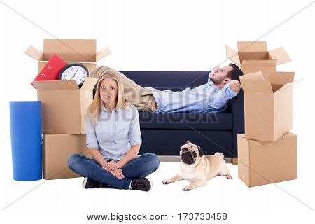 moving day concept - tired young couple with brown cardboard boxes with stuff and dog isolated on white background