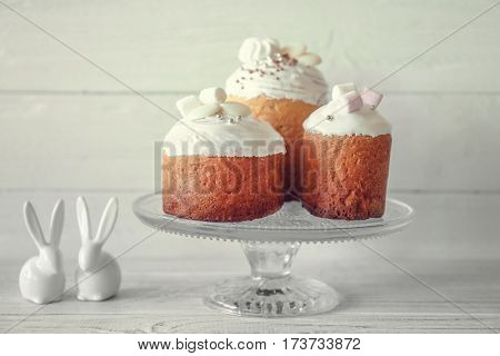 Easter cakes on stand on light background