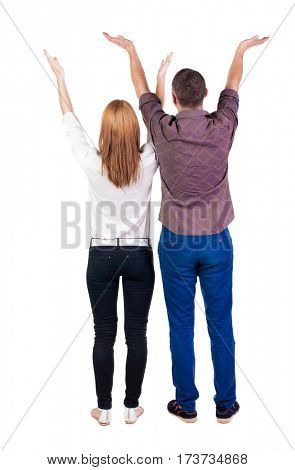 Back view couple  looking at wall and Holds  hand up. Rear view people. Isolated over white background.