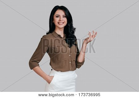 Confident and successful. Beautiful young woman in smart casual wear gesturing and looking at camera with smile while standing against grey background