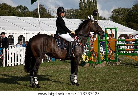 WEEDON, UK - AUGUST 28: A female show-jumper waits at the side of the arena before starting her round against the clock at the Bucks County show on August 28, 2014 in Weedon