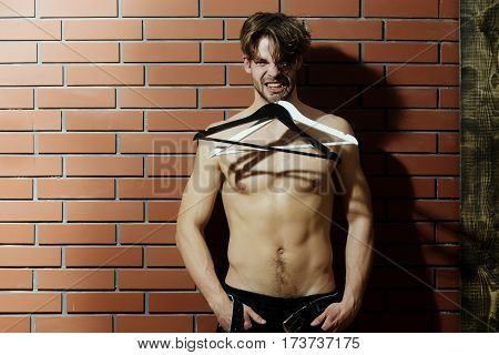 bearded macho man brutal caucasian hipster with moustache on aggressive face with muscular torso chest and body holds fashionable hangers on brick wall background