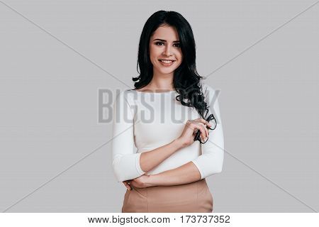 Confident woman. Beautiful young woman in smart casual wear keeping arms crossed and smiling while standing against grey background