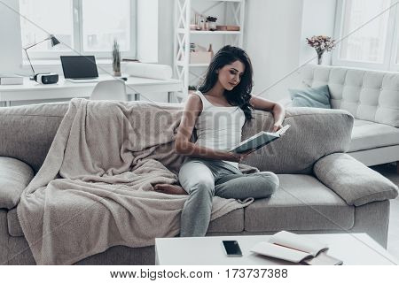 Engrossed in good book. Beautiful young woman reading a book while sitting on sofa at home