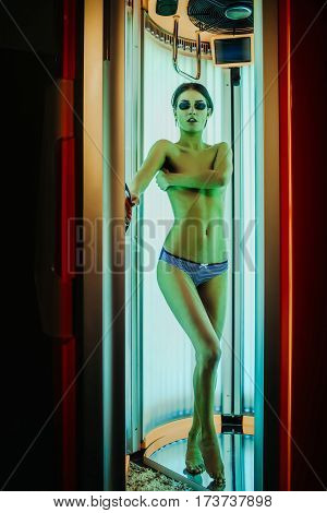 pretty naked woman or cute girl with sexy healthy body standing in solarium spa salon in pants and sunglasses has beautiful belly and chest