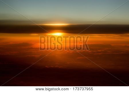 Thick soft clouds on idyllic grey sky celestial sphere in slanting rays of setting sun on orange overcast background. Upper layers of atmosphere