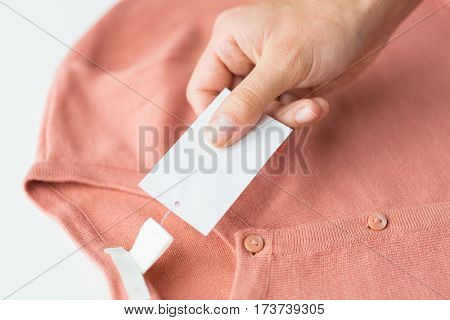 clothes, fashion, people and shopping concept - close up of hand holding price tag of clothing item