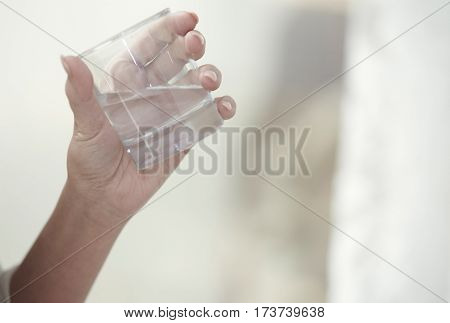 Hand of woman holding glass with potable water