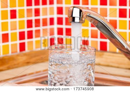 Point of view shot of a man pouring a glass of fresh water from a kitchen faucet