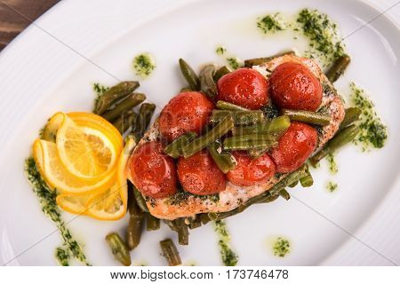 Grilled trout with tomatos leguminous beans and lemon on white plate. Top view