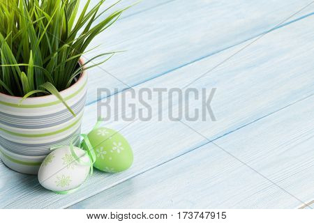 Easter eggs and potted plant on wooden background with copy space