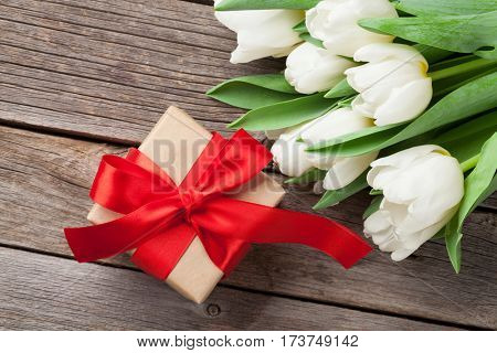White tulips bouquet and gift box on wooden background. Top view