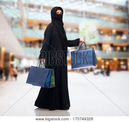 sale, consumerism and people concept - muslim woman in hijab with shopping bags over shopping center background