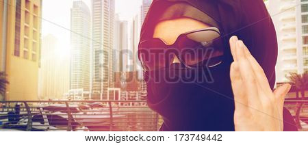 accessory, fashion and people concept - close up of muslim woman in hijab and sunglasses over dubai city street background