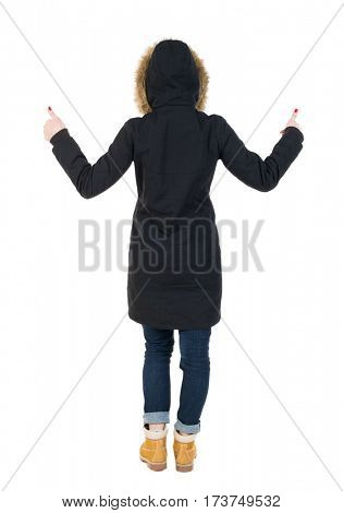 Back view of  woman  in parka thumbs up. Rear view people collection. backside view of person. Isolated over white background. Girl in a black winter jacket with  hood with two hands showing thumbs up