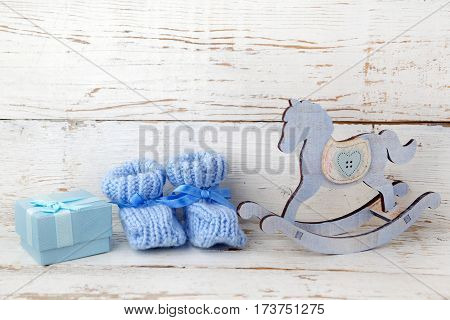 Blue booties for the baby on a wooden background of blue gift box and wooden horse.